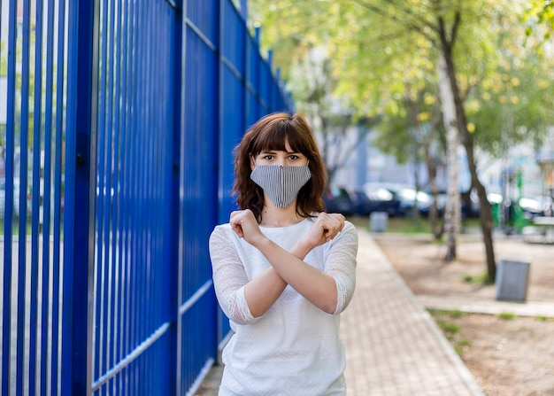 A girl in a medical mask stands on the street with her arms crossed. a young brunette girl shows a forbidding sign with her hands Premium Photo