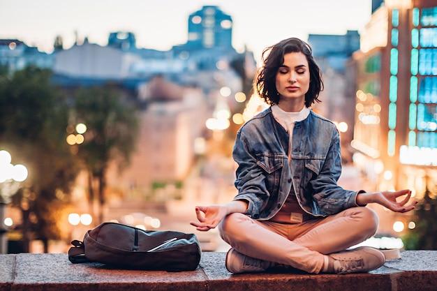 Girl meditating on background of evening city Premium Photo