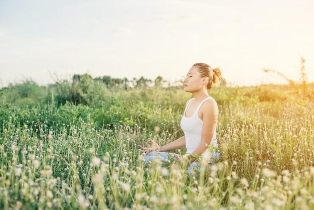 Girl meditating at sunset Free Photo