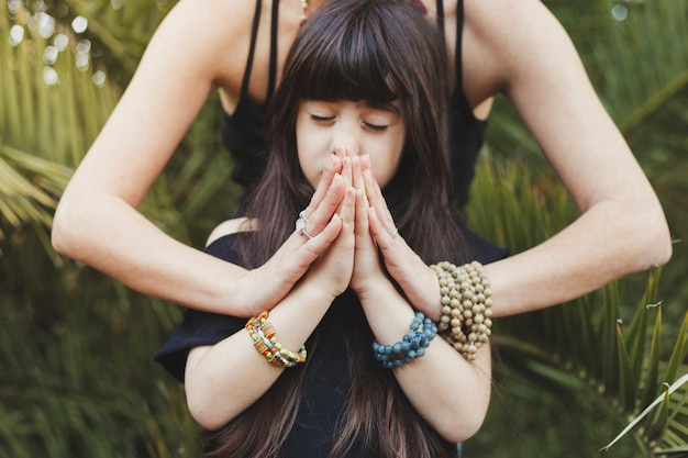 Girl meditating with mother Free Photo