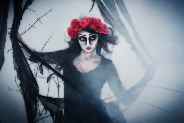 Girl mime in fog in forest, halloween. a wreath of flowers on head of woman, dark scary woods Premium Photo