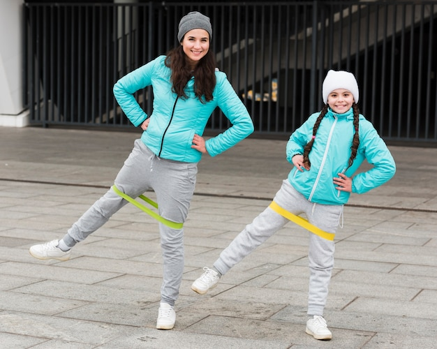 Girl and mom training with elastic bands Free Photo