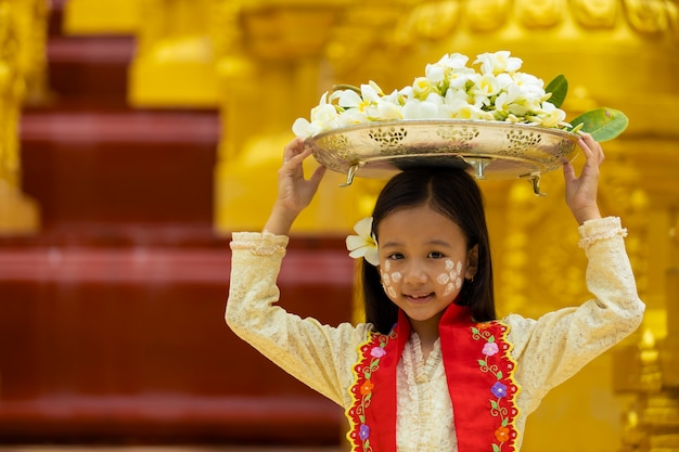 The girl in the mon national costume is presenting a flower-sized tray to offer to the monk on a religious day. Premium Photo