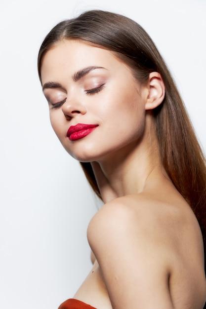 Девушка обнаженные плечи красные губы закрытые глаза чистая уход за кожей Premium Фотографии