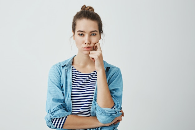 Girl need to find answer. charming young caucasian woman with bun hairstyle holding fingers on cheek and chin, looking seriously and troubled , thinking or deciding something in mind Free Photo