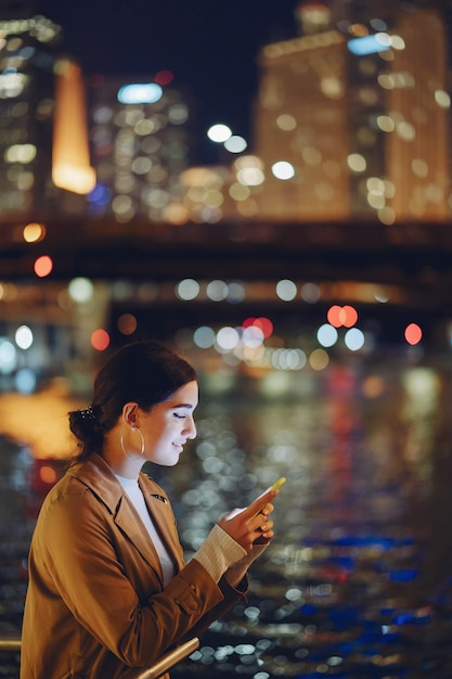 Girl at night with phone Free Photo
