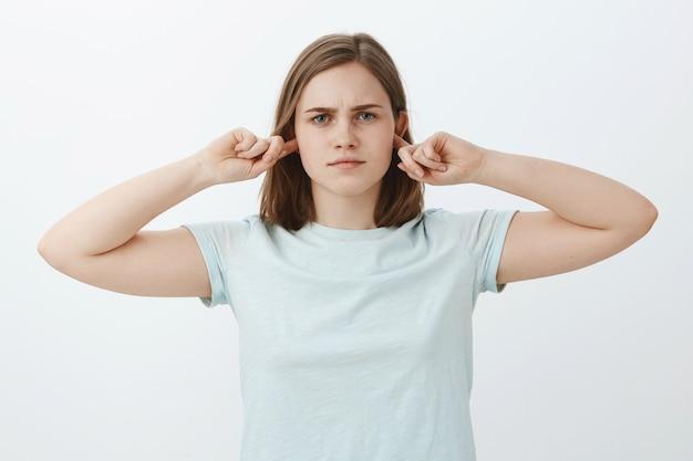 Девушка не собиралась слушать, заткнув уши. напряженная серьезная обеспокоенная женщина, закрывающая слух указательными пальцами и стоящая равнодушно и безучастно, не желая продолжать разговор Бесплатные Фотографии
