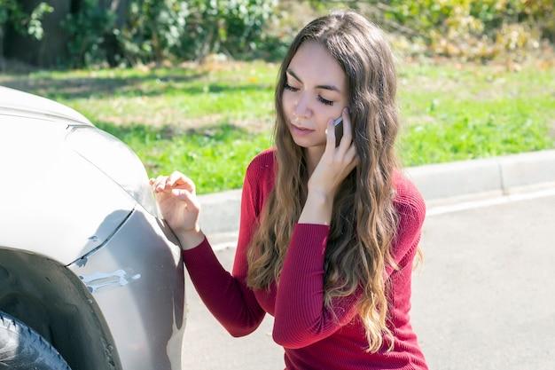女の子は車のバンパーに新鮮な傷があることに気づき、動揺しています。そして彼女は警察と保険に電話します Premium写真