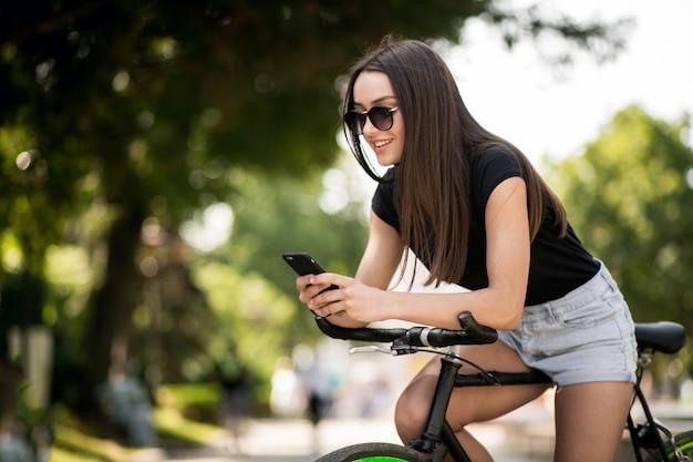 電話で自転車に乗る少女 無料写真