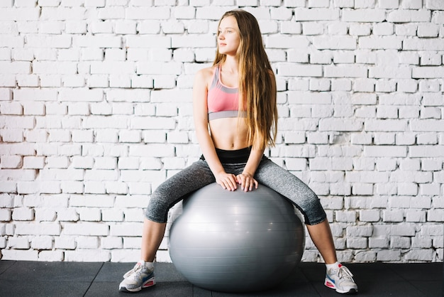 Girl on pilates ball against brick wall 23 2147688103