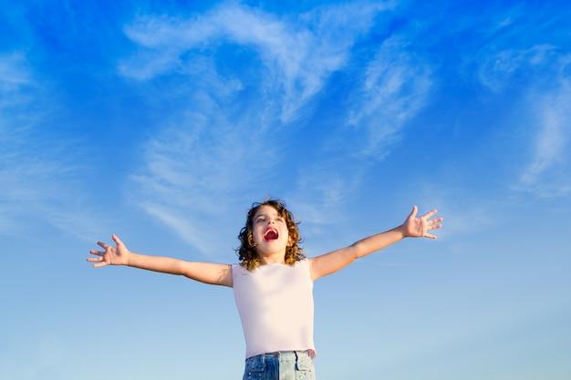 Girl open arms outdoor under blue sky Premium Photo