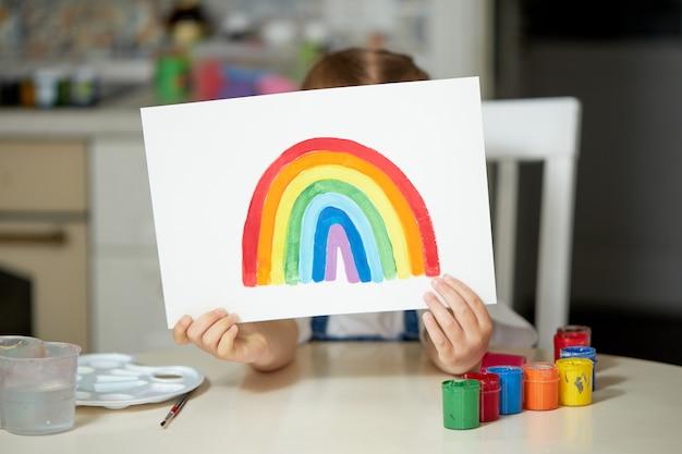 家で虹を描く少女 Premium写真
