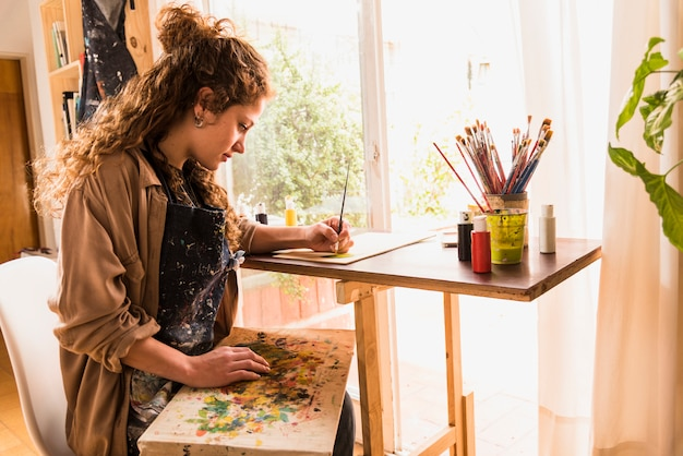 Girl painting a canvas Free Photo
