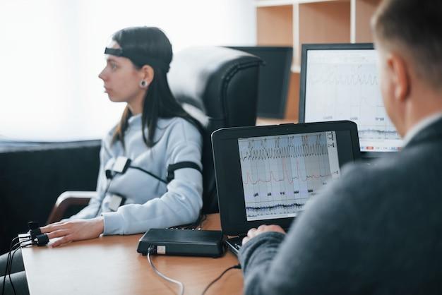 La ragazza passa la macchina della verità in ufficio. fare domande. test del poligrafo Foto Gratuite