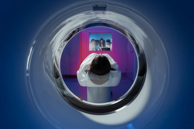 The girl patient is lying in the tomograph and waiting for a scan. Premium Photo