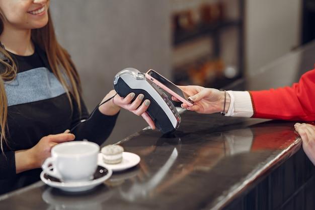 非接触型pay passテクノロジーを使用してスマートフォンでラテの支払いをしている女の子 無料写真
