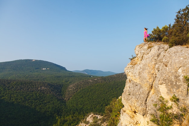 A girl in a pink dress stands on a rock in front of a precipice Premium Photo