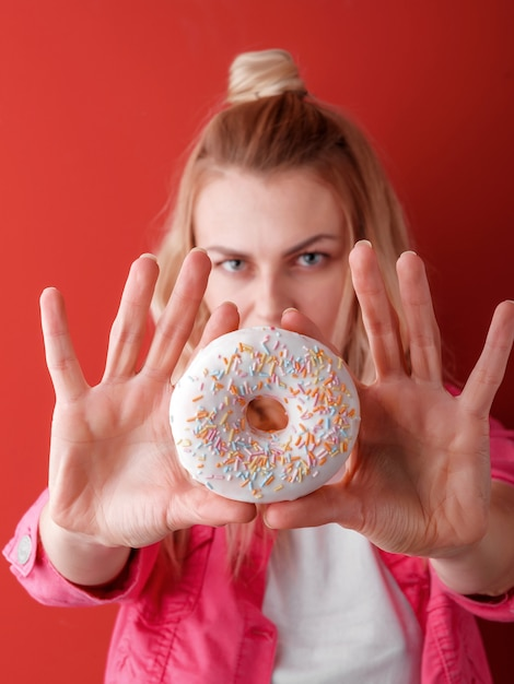 Girl in pink jacket on red background with donut in hands Premium Photo