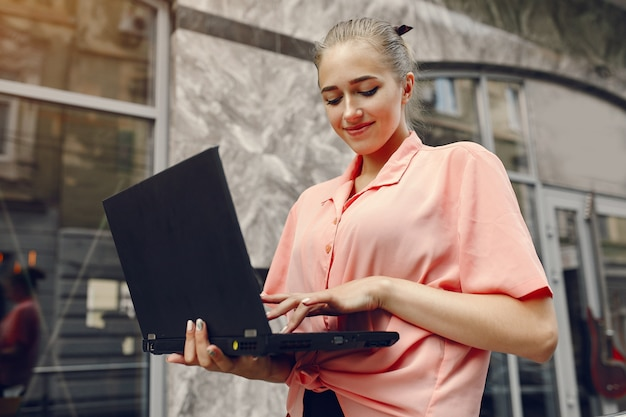 Girl in a pink shirt sitting near house and use the laptop Free Photo