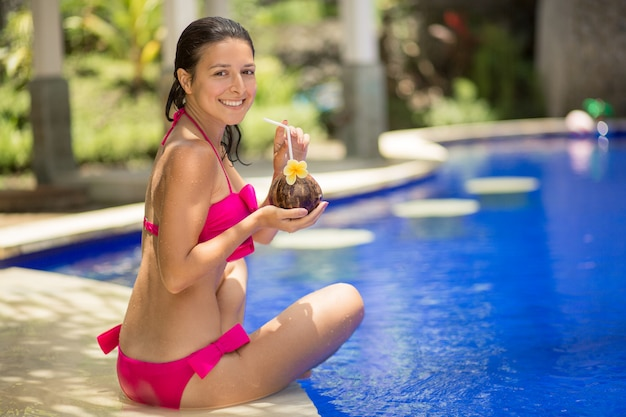 The girl in the pink swimsuit is resting on the edge of the pool with a drink from a coconut. Premium Photo