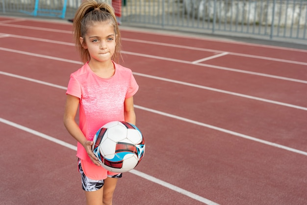 Girl in pink t-shirt holding football Free Photo