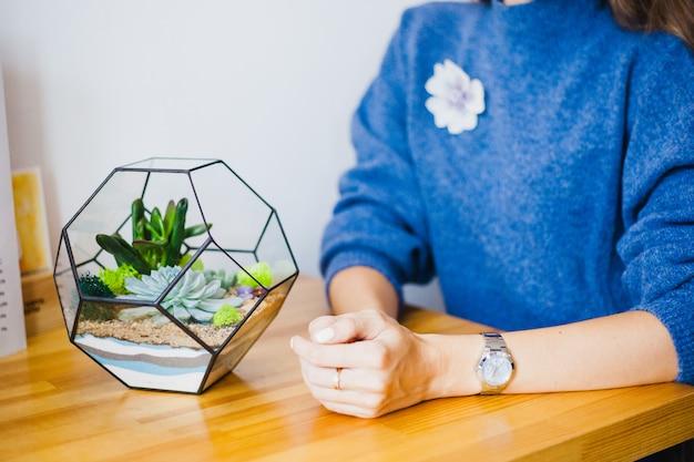 The girl plants a glass form, planting flowers, glass terarium Premium Photo