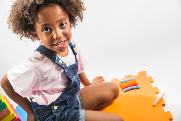 Girl on play mat with plasticine in studio Free Photo