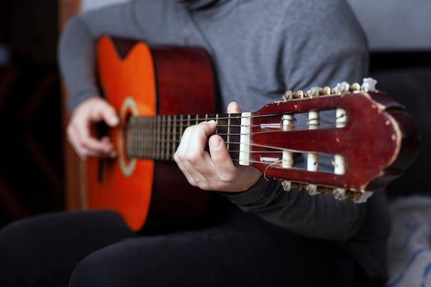 Девушка играет шестиструнная акустическая гитара с нейлоновыми струнами. Premium Фотографии