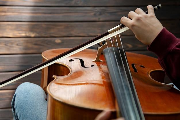 Девушка играет на виолончели на деревянном полу Premium Фотографии