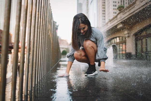 Girl playing and dancing around on a wet street Free Photo