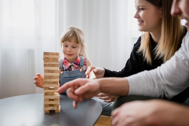 Girl playing jenga with crop parents Free Photo