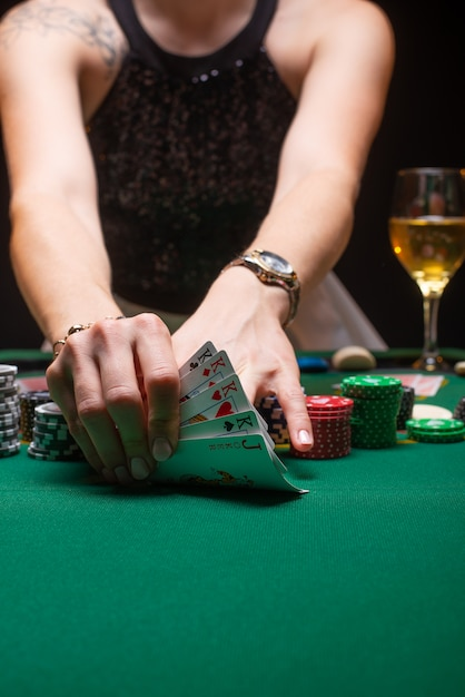 Girl playing poker and looking at cards Premium Photo