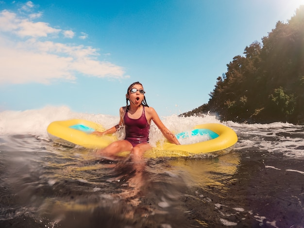 Girl playing in the sea with the airbed Premium Photo