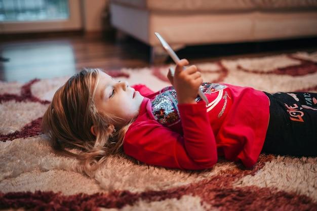 Girl playing tablet game on carpet Free Photo