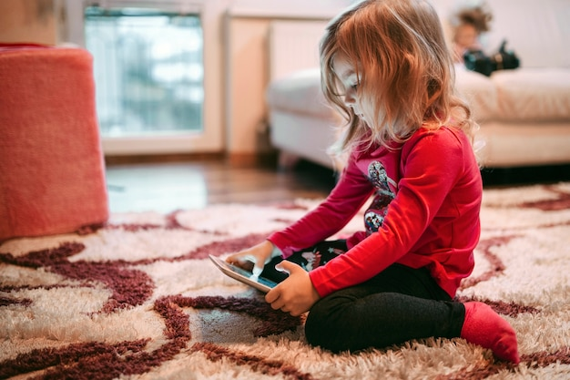 Girl playing tablet game on floor Free Photo