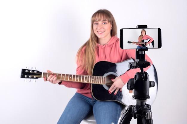 ギターを弾いてソーシャルネットワークで共有する女の子 Premium写真