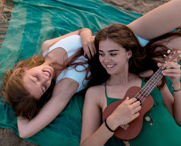 Girl playing ukulele for her friend while lying on beach Free Photo