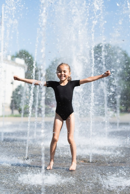 Girl playing at water fountain Free Photo
