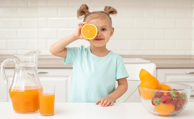 Ragazza che gioca con l'arancia a casa Foto Gratuite