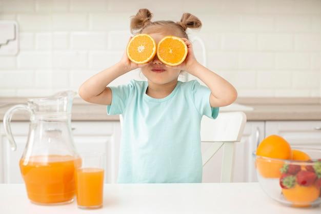 Ragazza che gioca con l'arancia Foto Gratuite