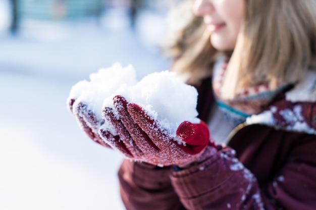 公園で雪で遊ぶ女の子。雪の冬の服を着て幸せな女の子の肖像画 Premium写真