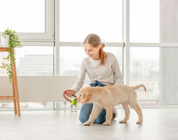 Девушка играет с молодой собакой Premium Фотографии