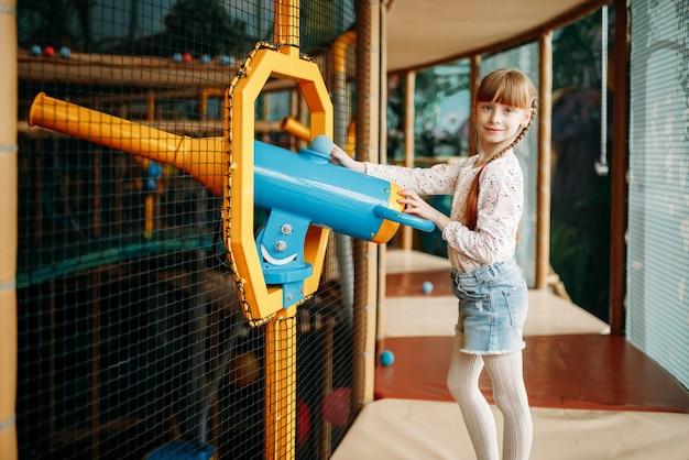 子供のゲームセンターでエアガンで遊ぶ女の子 Premium写真
