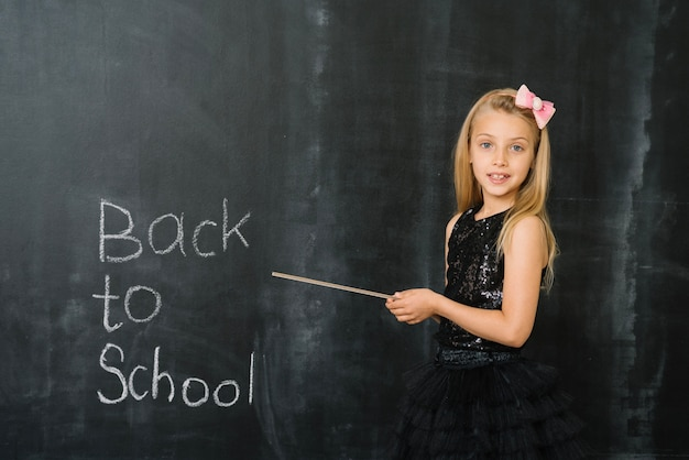 Girl pointing on blackboard Free Photo