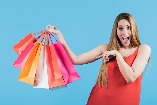 Girl pointing at shopping bags Free Photo