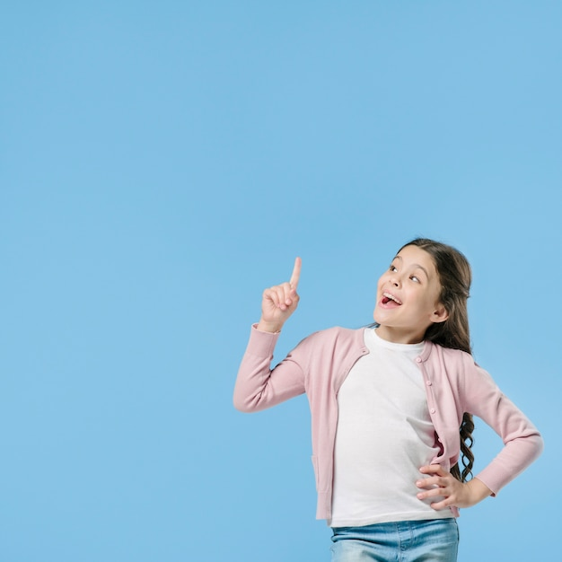 Girl pointing standing in studio Free Photo
