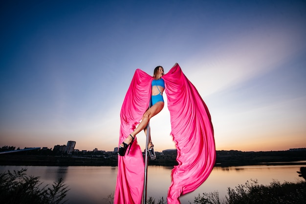Girl pole dancer performs an element on the pole with wings and beautiful flying, flowing fabric Premium Photo