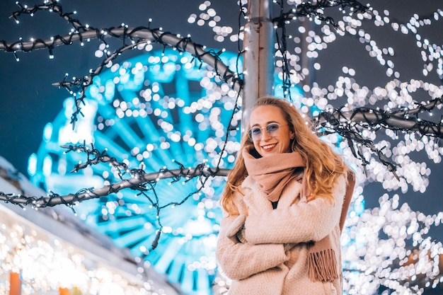 Girl posing against the background of decorated trees Free Photo