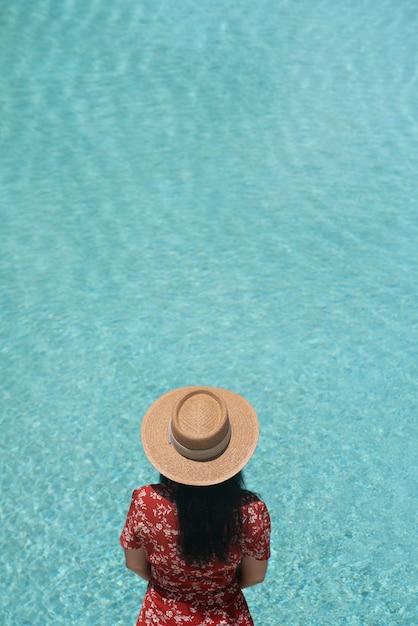 Девушка позирует возле бассейна в модном купальнике с отражением в бассейне на заднем плане / летняя активность Premium Фотографии