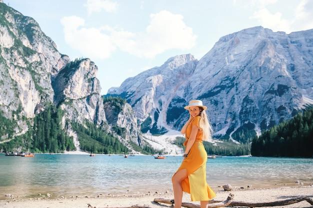 アルプスの風光明媚な山の湖のほとりでポーズをとる少女。ドロミテ、イタリア、ヨーロッパのブラーイエス湖の眺め。 Premium写真